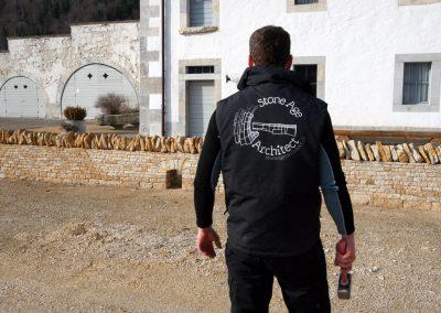 Une personne qui se trouve en face du mur de pierres sèches à Bellelay, avec le logo de Stone Age Architect sur le dos de son gilet