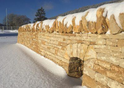 Une partie du mur de pierres sèches dans la neige pendant une journée ensoleillée