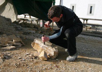 Ein Mann beim Meisseln eines Kalksteines aus dem Jura